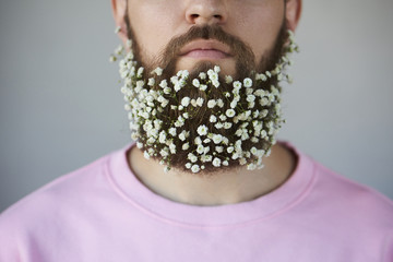 closeap of handsome man with flowers in beard on gray background