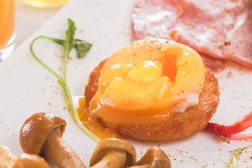 poached egg with a flowing yolk on a crispy toast with mushrooms, ham and greens. Fresh juice, sauce. Low morning light