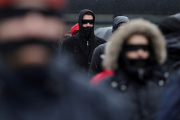 Romanians sporting black cloths over their mouths and eyes protest against the ruling leftist Social Democrat party plans to overhaul judicial legislation in Bucharest