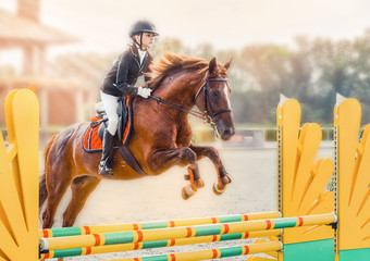 Young girl in uniform jumping with sorrel horse. Blond pretty little girl going jump a hurdle in a...