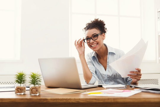 Happy business woman reading document at office desktop
