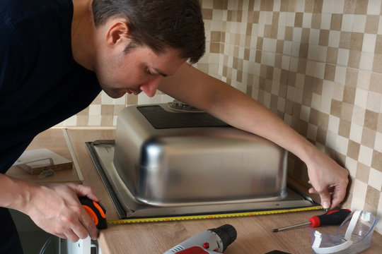 Stainless steel kitchen sink installation by man. Renovation of the kitchen.