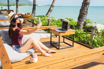 Woman sitting in beach cafe with laptop and coconut and making selfie.