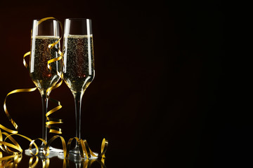 Champagne glasses with ribbon on black background