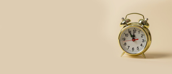 Golden clock on a light brown background