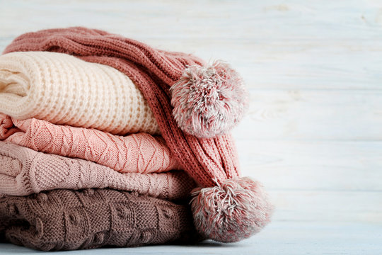 Stack of knitted sweaters and scarf on wooden table