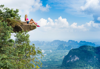 Happy young girl sitting on the top of mountain with a breathtaking view of the landscape with valley and rocks.