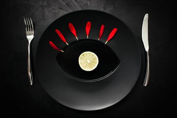 Matte black plate decorated with red petals. Strict weightloss diet. All-seeing eye concept