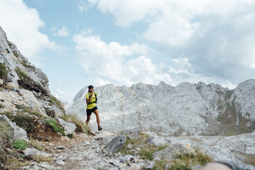 Front view of a ultra trail runer running on a cloudy day close to Collado Jermoso, Leon, Spain