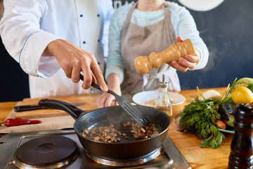 Close up of two unrecognizable chefs working in kitchen, roasting mushrooms and adding salt and pepper in modern open kitchen