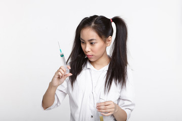 Serious concentrated young Chinese female chemist with two ponytails holding test tube with liquid solution in one hand and looking at syringe in other while carrying out laboratory experiment