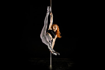 Young and sexy woman exercises pole dance on the dark background