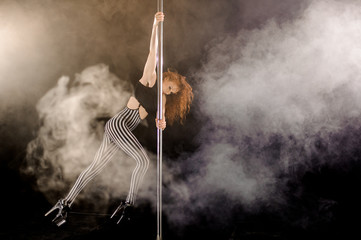 Red haired sexy pole dance girl exercises and poses on the pylon in the smoke