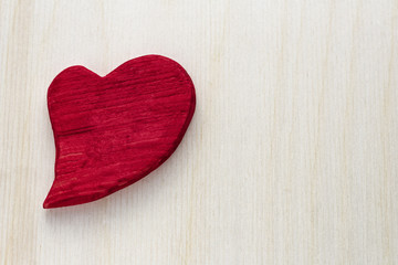 Wooden red heart on wooden background.
