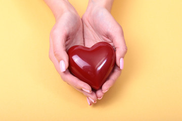 Female hands giving red heart, isolated on gold background, christmas winter love