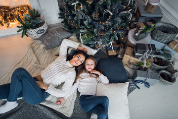 Beautiful happy family mother and daughter with gifts around christmas tree are on the floor together at home