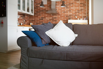 Gray sofa with kitchen on background