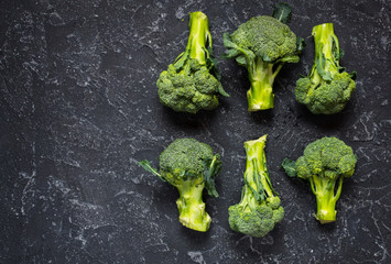 Raw broccoli on black stone background. Top view and text space