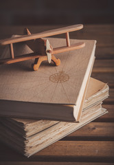 Vintage wooden airplane toy and old books