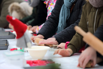 Ręce i dłonie ludzi na stole w czasie ugniatania i wałkowania ciasta.