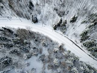 Aerial view of railroad through winter forest with snow covered trees in Switzerland
