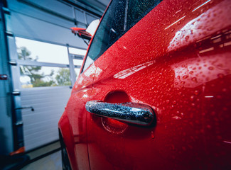 Details of electric car. Door handle and rain drops. Red color