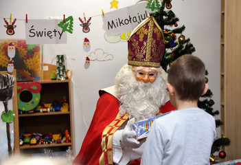Święty Mikołaj wręcza prezent chłopcu w przedszkolu.