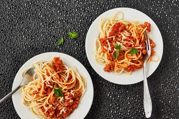 Italian pasta bolognese. Spaghetti with minced meat and tomato sauce in a white plate. Top view