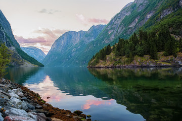 Golden sunrise in the mountains, Gudvangen Norway with reflection in the water of the fjord.