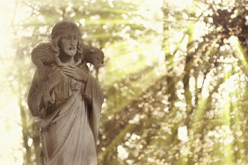 Ancient statue of Jesus Christ Good Shepherd in sun rays (faith, religion, Christianity, God concept)