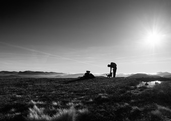 A black and white image of a hiker and their dog on a summit on a cold winters morning in the Derwent Fells, English Lake Distrct, UK.