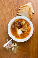 Borsch, ready-made dish on the table. Soup from beets, potatoes, cabbage and meat on a wooden table close-up.