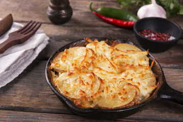 potato casserole with cheese in a frying pan serving vegetarian dish homemade