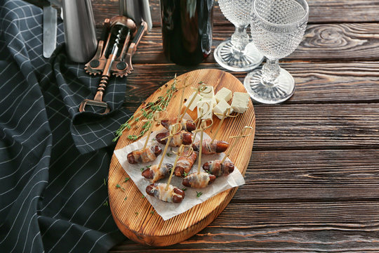 Wooden board with bacon wrapped dates on table