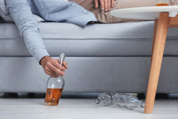 Drunk man lying on sofa with bottle of whiskey in hand. Alcoholism concept