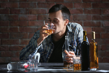 Man drinking whiskey and smoking cigarette while sitting at table. Alcoholism concept