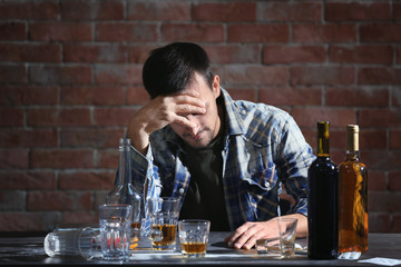 Drunk man sitting at table with alcohol and drugs. Alcoholism concept