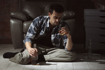 Man sitting on floor at home and drinking whiskey. Alcoholism concept