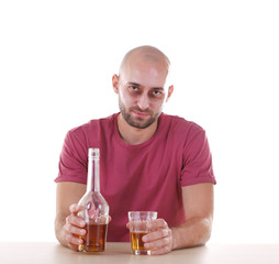 Drunk man sitting at table with whiskey against white background. Alcoholism concept