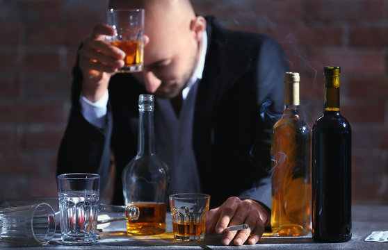 Man drinking whiskey and smoking cigarette at table. Alcoholism concept
