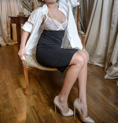 Sexy lady in white shirt and tight black skirt and elegant high heels. Attractive woman dressing up, sitting on chair. Sensual revealing of white lingerie and white pearls.