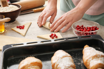 Woman preparing puff pastry at table