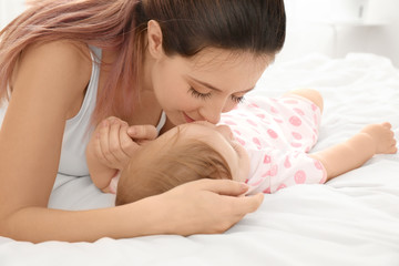 Young mother kissing her cute baby on bed