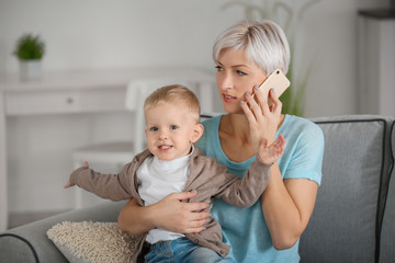 Young mother talking on phone while holding her baby at home