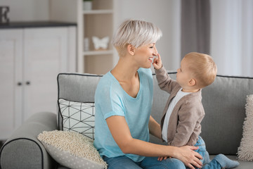 Attractive young mother playing with her baby on couch at home