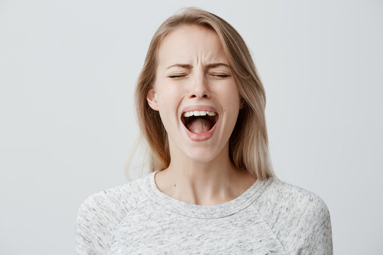 Emotional blonde woman opening her mouth widely screaming loudly being dissatisfied with something expressing disagreement and annoyance. Female shouting at boyfriend, Negative emotions and feelings