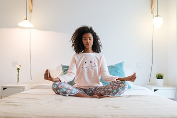 Happy beautiful young black woman relaxed  at home doing morning meditation in bed .