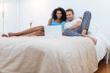 Happy young couple relaxed at home lying down in bed on the computer