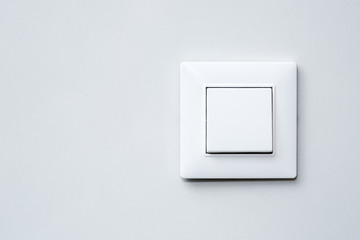 a light switch on gray wall.