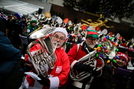 A man dressed as Santa Claus joins hundreds of tuba players as they perform Christmas carols during the 44th Annual Merry Tuba Christmas at Rockefeller Center in the Manhattan borough of New York